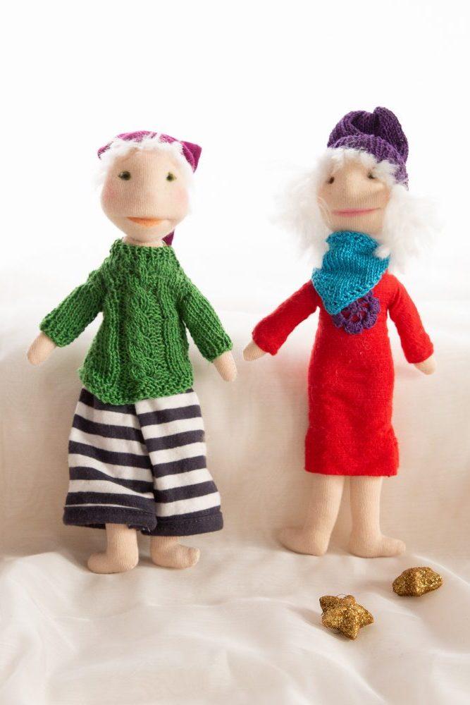 handgroße Minipuppen bzw. Pixies, das Mädchen im roten Jerseykleid, mit lila Blüte, lila Mütze und türkisem Halstuch, er mit marineblau gestreifter weiter Hose und grünem Strickpulli und Mütze, beide barfuß