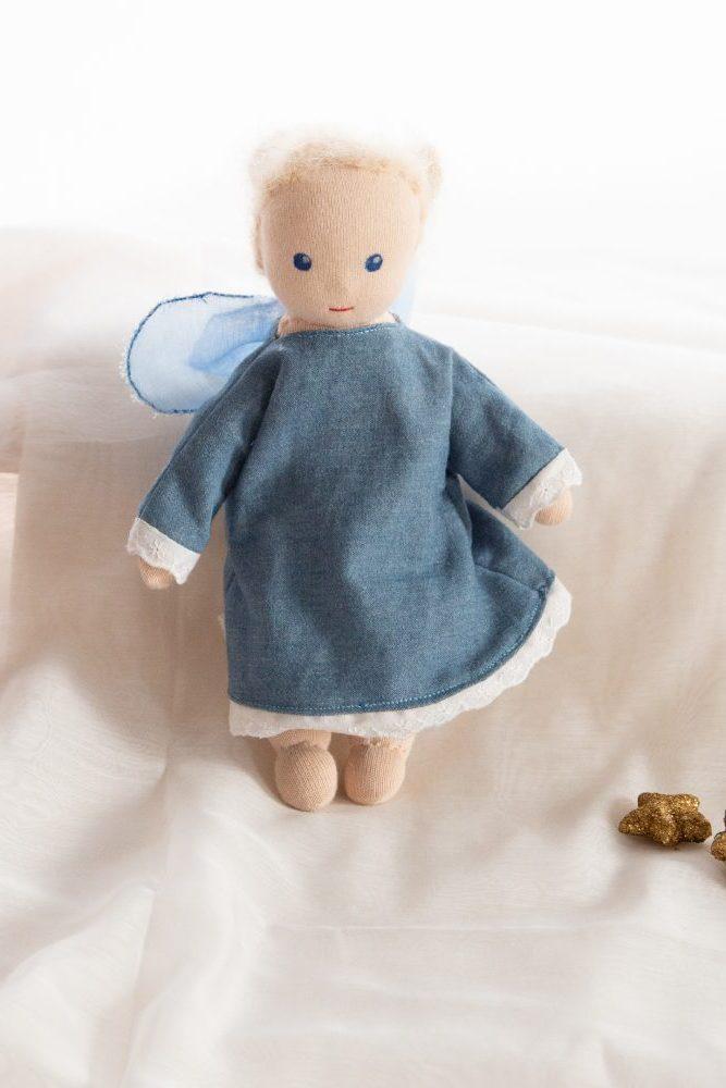 handgroßes Puppenwesen mit Jeanskleid und weißer Stoffspitze am Kleidersaum und an den Ärmeln, barfuß, blonde Aufsteckfrisur, blaue Augen, hellblaue Elfenflügel