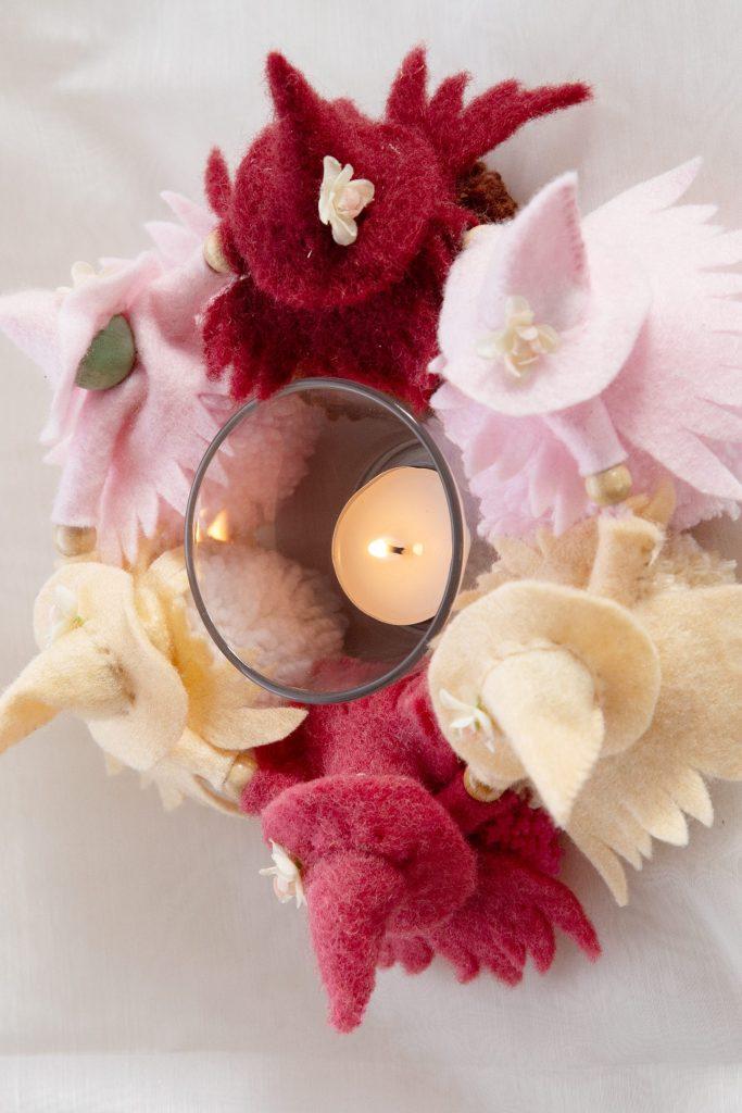 handgemachte Wesen mit unterschiedlich rosa getönten spitzen Filzhüten, die sich an den Händen halten und einen Kreis bilden, die Körper sind aus flauschiger unterschiedlich gefärbten altrosa Wollpompons, sie tanzen um ein flackerndes Kerzenlicht