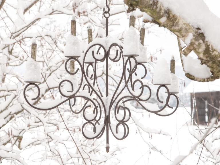 gusseiserne Kerzenlampe, die in der Birke hängt, frisch gefallener Schnee verleiht ihr mit seinen Häubchen einen ganz eigenen Reiz