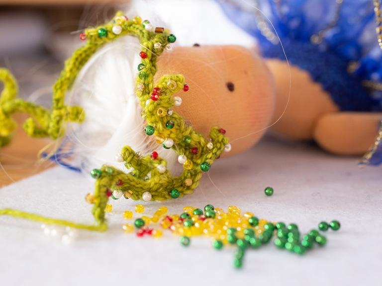 Glasperlen werden auf den gehäkelten Kopfkranz für Lucia gestickt, sie wartet geduldig und schon sehr gespannt auf diesen schönen Kopfschmuck anlässlich der Wintersonnenwende