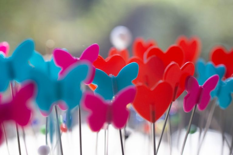 rote, türkise und purpurene Plastikschmetterlinge auf Stecknadeln