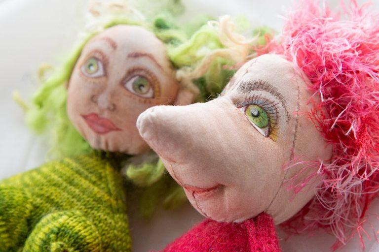 Pinkhaariger Puppenkopf und riesiger Nase und grünen Augen rechts, links grünhaariger Puppenkopf mit grünen Augen, handgemalt, handgenäht und gestrickter Körper, den man angeschnitten sieht