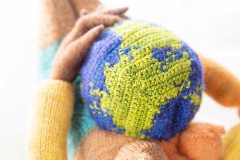 gehäkelter Planet Erde in der gefilzten Hand eines Wesens, das Mother Earth heißen wird