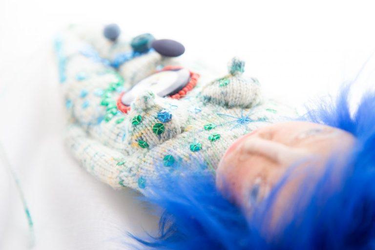 blauhaariges Wesen mit weiß-türkisfarbenem Strickkörper, bestickt mit Pailletten in Grün, Blau und Türkis, stilisierte Yoni, die mit roten Perlen umstickt ist