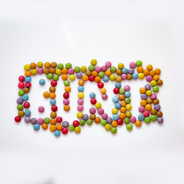 viele bunte Smarties, durch Auslassungen entsteht das Wort BUNT auf dem weißen Untergrundpapier