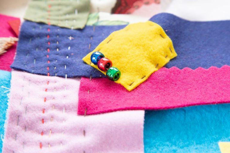 eine blaue, rote und grüne Plastikperle auf gelbem Rechteck, das alles auf Ebenen von vielen anderen Farben, handgenähter Quilt
