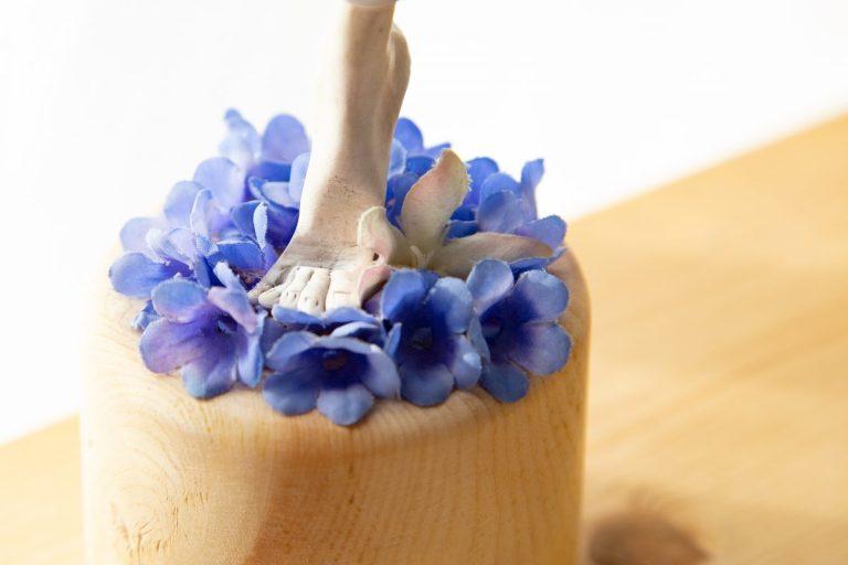 Rattenfuß aus Zehenspitzen im Glockenblumenblütenmeer auf Holzständer