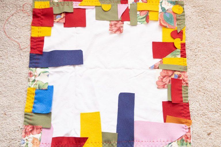 angefangener Kwandi Quilt, weiße Basisfläche, zwei bunte Reihen rundherum, handgenäht mit Steppstichen