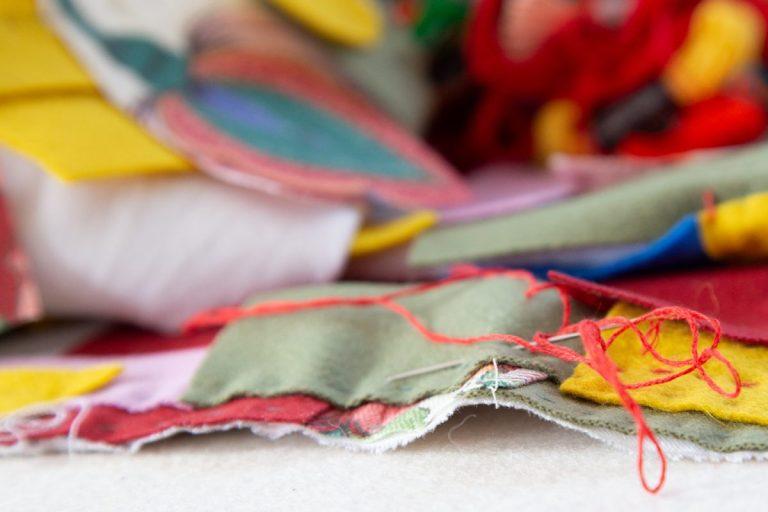 eine Nadel mit rotem Faden durchsticht bunte Filzfarbschichten eines handgenähten Quilts