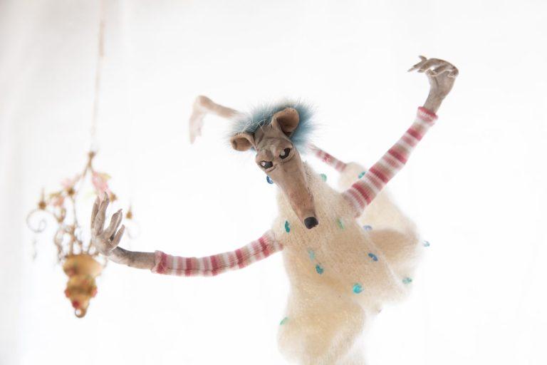 filigrane, tanzende Ratte, Arme sind oben, ein Bein nach hinten hinaus gestreckt, der vordere Fuß auf Zehenspitzen und durchgestreckt, vorherrschende Grundfarben Weiß, Türkis und Rosatöne