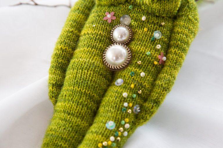 stilisierte Yoni aus Perlmuttknöpfen mit Goldrand, auf gestricktem grünen menschlichem Körper