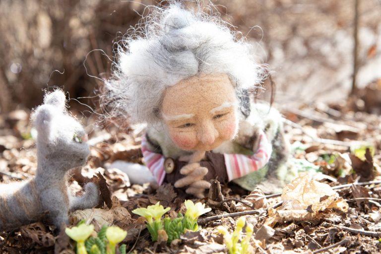 Emely, angegraute Hippie-Frau, gefilzt, liegt vor den diesjährigen gelben Primeln, die aus der Erde schauen, gut bewacht von ihrem Kater